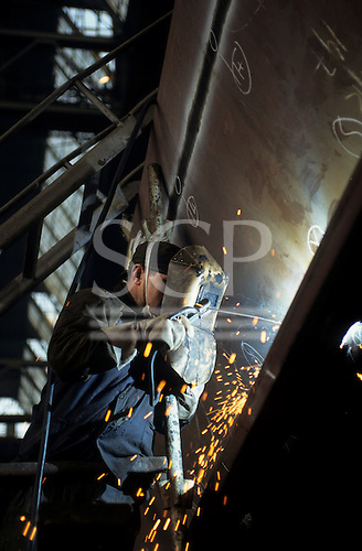 Gdansk, Poland. Shipyard worker welding with electric arc welder and protective face mask.