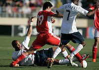 Oguchi Onyewu attempts a slide tackle on China's Dong Fangzhuo as DaMarcus Beasley closes in. The USA defeated China, 4-1, in an international friendly at Spartan Stadium, San Jose, CA on June 2, 2007.