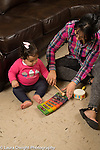 12 month old baby girl with mother, sitting on floor, mother demonstrating how to hit toy xylophone with mallet