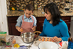 3 year old boy in kitchen at home with mother learning to cook baking, cracking egg against bowl