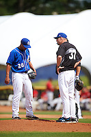 Biloxi Shuckers pitching coach Chris Hook (37) talks with pitcher Hiram Burgos (26) during a game against the Birmingham Barons on May 24, 2015 at Joe Davis Stadium in Huntsville, Alabama.  Birmingham defeated Biloxi 6-4 as the Shuckers are playing all games on the road, or neutral sites like their former home in Huntsville, until the teams new stadium is completed in early June.  (Mike Janes/Four Seam Images)