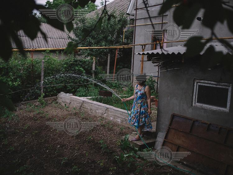 Angela, watering her vegetable garden.