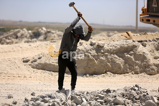 Palestinian workers crush stones and cement blocks from houses marking International Workers' Day, in Gaza city on May 01. 2021. Youth (19- 29 years) are the most group suffering from unemployment. Thus, the unemployment rate among youth reached about 39%; 24% in the West Bank and 67% in Gaza Strip. Moreover, the youth graduates of those who hold a scientific qualification of an intermediate diploma or higher are the most group suffering from unemployment, as this rate reached about 54%; (36% in the West Bank and 79% in Gaza Strip). Photo by Dawoud Abo Alkas