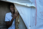 A woman in the doorway to her tent home in the Petionville Camp at the edge of Port au Prince, Haiti. With some 50,000 residents packed onto what was once a golf course, it's the largest camp of hundreds of locales hosting more than a million people left homeless by the January 12, 2010 quake.