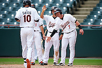 Bowie Baysox center fielder Glynn Davis (10) is greeted at home by Drew Dosch (11), Adrian Marin (1), and Joey Terdoslavich (7) after hitting a grand slam home run during the second game of a doubleheader against the Akron RubberDucks on June 5, 2016 at Prince George's Stadium in Bowie, Maryland.  Bowie defeated Akron 12-7.  (Mike Janes/Four Seam Images)