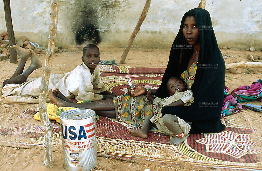 Sudan.  Abu Zhar. Abu Zhar is located on a school compound in the town of Al Geneina and is a camp for internally displaced people (IDP) from the civil war. A mother and her two children, a boy and a girl, are seated on a carpet on the ground. A empty can of vegetable oil, given by America to feed the population suffering from the ongoing civil war, is laid on the flour. © 2004 Didier Ruef