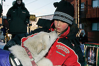 Thursday  March 15, 2007   ---- Nome, Alaska.  Mitch Seavey's son Conway, pets a Jim Lanier dog after Jim arrived in Nome in 28th place.