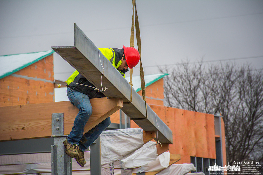 Steelworker bolts into place a beam at the entrance to Northstar Cafe.
