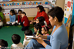 Education Preschool 3-5 year olds feamale teacher making written observations of class at circle time horizontal
