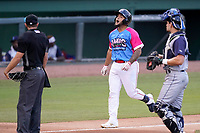"""Catcher Alan Marrero (1) of the Greenville Drive reacts after hitting a home run in a game against the Brooklyn Cyclones on Saturday, May 15, 2021, at Fluor Field at the West End in Greenville, South Carolina. Drive players were wearing jerseys for the """"Ranas de Rio de Greenville"""" (Greenville River Frogs), as part of Minor League Baseball's """"Copa de la Diversion."""" The umpire is Adam Clark and the catcher is Hayden Senger (24). (Tom Priddy/Four Seam Images)"""
