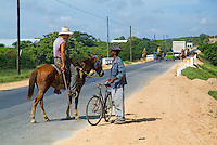 Cowboy talking to a man with a bicycle on the side of a rural road in Cuba.