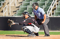 Catcher Kellin Deglan #15 of the Hickory Crawdads sets a target as home plate umpire Ivan Mercado looks on during the South Atlantic League game against the Kannapolis Intimidators at Fieldcrest Cannon Stadium on April 17, 2011 in Kannapolis, North Carolina.   Photo by Brian Westerholt / Four Seam Images
