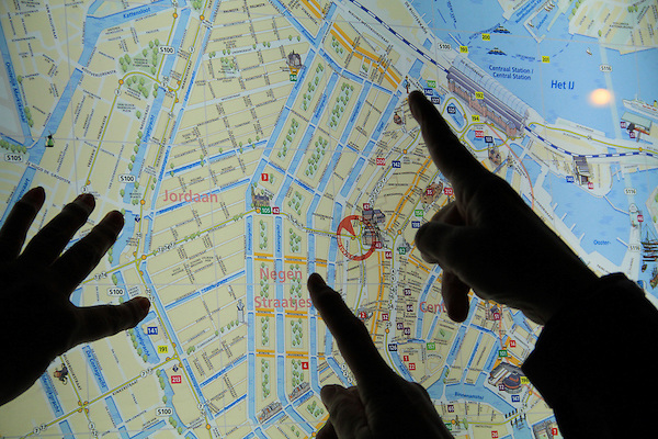 Visitors looking at map of Amsterdam, Netherlands.