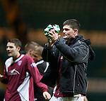 Derek Holmes celebrates to the Arbroath fans clutching a Celtic players shirt as a souveneir