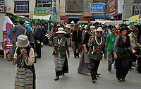 The famous Barkhor street where the old and new meets, traditional Tibetans with their prayer wheel on the way to the Jokhang Temple ,Lhasa, Tibet,.The Jokhang Temple is one of Tibet's holiest shrines, originally built in 647 A.D. in celebration of the marriage of the Tang Princess Wencheng and the Tubo King Songtsen Gampo. In front of the gate is a stone Tablet of Unity from the Tang Dynasty; inscribed are both Chinese characters and Tibetan script. Nearby is the stump of the willow tree said to have been planted by Princess Wencheng herself; two younger willow trees now flank the stump of the first tree...Located in the center of old Lhasa, the temple was built by craftsmen from Tibet, China, and Nepal and thus features different architectural styles. The temple is also the spiritual center of Tibet and the holiest destination for all Tibetan Buddhist pilgrims. In the central hall is the Jokhang's oldest and most precious object--a gold statue of a seated 12-year-old Sakyamuni. This is said to have been transported to Tibet by Princess Wencheng from her home in Changan in 700 A.D. Other precious antiques in the temple include a silk portrait of Buddha from the Tang Dynasty and a pearl gown and gold lamp from the Ming Dynasty. The three-leafed roof of the Jokhang offers splendid views of the bustling Barkhor market and across to the Potala Palace..