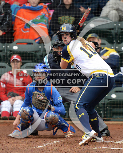 Michigan Wolverines pitcher Sara Driesenga (10) at bat in front of catcher Aubree Munro (1) and umpire Tyrone Miller during the teams season opener against the Florida Gators on February 8, 2014 at the USF Softball Stadium in Tampa, Florida.  Florida defeated Michigan 9-4 in extra innings.  (Mike Janes/Four Seam Images via AP Images)