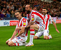 1st October 2021;  Bet365 Stadium, Stoke, Staffordshire, England; EFL Championship football, Stoke City versus West Bromwich Albion; Steven Fletcher of Stoke City picks under pressure from Nick Powell to celebrate his 77th minute goal
