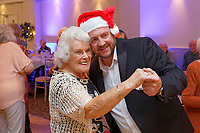 Pictured: Lottery winner Nigel Willett (R) from Caerphilly dances with Dilys Sutton, 87.  Wednesday 28 November 2018<br /> Re: National Lottery millionaires from south Wales and the south west of England have hosted a glitzy Rat Pack-inspired Christmas party for an older people's music group at The Bear Hotel in Cowbridge, Wales, UK.