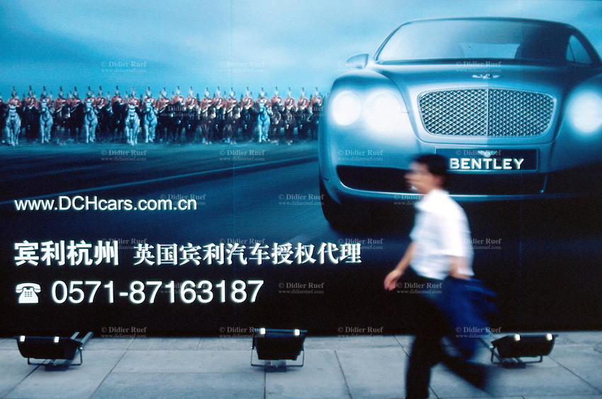 China. Province of Zhejiang. Hangzhou. A man walks near a big publicity campaign for the latest Bentley car. The british horse guards stand on the line with the fancy car. © 2004 Didier Ruef