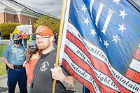 """A man wears a Keep America Great hat and carries a Three Percenter flag as people gather for an anti-lockdown protest organized by the alt-right group Super Happy Fun America near the home of Massachusetts governor Charlie Baker in Swampscott, Massachusetts, on Sat., May 16, 2020. The Three Percenters are a far-right American militia advocating gun rights and resistance to the federal government. The protest was in defiance of Massachusetts orders mandating face coverings and social distancing and prohibiting gatherings larger than 10 people during the ongoing Coronavirus (COVID-19) global pandemic. The state's stay-at-home order is expected to be updated on May 18, 2020, with a phased reopening plan issued by the governor as COVID-19 cases continue to decrease. Anti-lockdown protests such as this have become a conservative cause and have been celebrated by US president Donald Trump. Many of the protestors displayed pro-Trump messages or wore Trump campaign hats and shirts with phrases including """"Trump 2020"""" and """"Keep America Great."""" Super Happy Fun America, organizers of the protest, are an alt-right organization best known for creating the 2019 Boston Straight Pride Parade."""