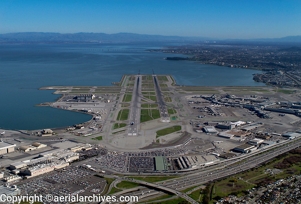 aerial photograph San Francisco International airport (SFO), San Francisco, California from the Bayshore Freeway down runways 10L and 10R toward the San Mateo bridge.