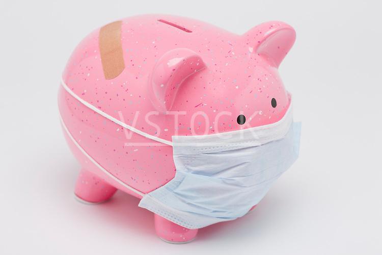 Piggy bank wearing surgical mask, studio shot