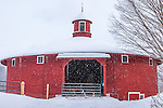 Fresh snow on thr red round barn in Barnet, VT