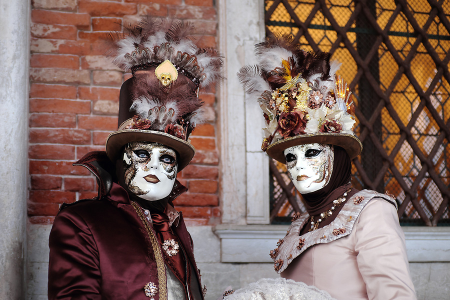 Couple dressed in traditional mask and costume for Venice Carnival standing at Doge's Palace, Piazza San Marco, Venice, Veneto, Italy