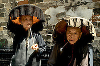 Old Hakka women with pipes in the old walled city of Kam Tin in the New Territories area of Hong Kong.  This is a dying breed of woman for tourists with black hats and black clothes with smoking