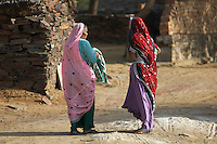 On the road from Mandava to Delhi, India women chatting in front otf traditional houses