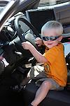A little boy sitting inside the driver's side of a police car greifenhagen