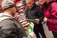 Am Samstag den 17. Januar 2015 wurde die erste Ausgabe der franzoesischen Satire-Zeitschrift Charlie Hebdo nach dem Mordanschlag am 7. Januar auch in Deutschland verkauft. Auf Grund der grossen Nachfrage in Frankreich wurden nur wenig Exemplare nach Deutschland geschickt. So sind in Berlin angeblich nur 125 Stueck zum Verkauf ausgeliefert worden.<br /> Am Berliner Hauptbahnhof haben Menschen seit dem Vorabend um 23.30 vor einem Zeitungsladen angestanden, um bei Oeffung um 5.00 Uhr eines der begehrten drei Exemplare zu bekommen, die dort angeliefert wurden.<br /> So kam es bei Ladenoeffung zum Teil zu tumultartigen Szenen, bei denen sich die wartenden gegenseitig im Preis ueberboten oder die Verkaeufer beschimpften, weil nur ein Exemplar in der Filiale war.<br /> Im Bild vlnr: Kenny Rebenstock und sein Freund Nico H. haben seit dem Vorabend gewartet und je eine der zwei Ausgaben der Charlie Hebdo bekommen die in der Bahnhofsbuchahndlung verkauft wurden. Die beiden sind extra aus Torgelow und Pasewalk in Mecklenburg Vorpommern gekommen.<br /> Rechts: Eine junge Frau versucht einem der Beiden mit viel Charme ein Exemplar abzukaufen.<br /> 17.1.2015, Berlin<br /> Copyright: Christian-Ditsch.de<br /> [Inhaltsveraendernde Manipulation des Fotos nur nach ausdruecklicher Genehmigung des Fotografen. Vereinbarungen ueber Abtretung von Persoenlichkeitsrechten/Model Release der abgebildeten Person/Personen liegen nicht vor. NO MODEL RELEASE! Nur fuer Redaktionelle Zwecke. Don't publish without copyright Christian-Ditsch.de, Veroeffentlichung nur mit Fotografennennung, sowie gegen Honorar, MwSt. und Beleg. Konto: I N G - D i B a, IBAN DE58500105175400192269, BIC INGDDEFFXXX, Kontakt: post@christian-ditsch.de<br /> Bei der Bearbeitung der Dateiinformationen darf die Urheberkennzeichnung in den EXIF- und  IPTC-Daten nicht entfernt werden, diese sind in digitalen Medien nach §95c UrhG rechtlich geschuetzt. Der Urhebervermerk wird gemaess §13 UrhG verlangt.]