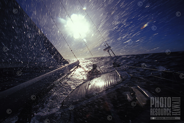 """Sailing yacht """"Heron"""", water spraying over deck in rough ocean, off Oahu, Hawaii during a storm"""