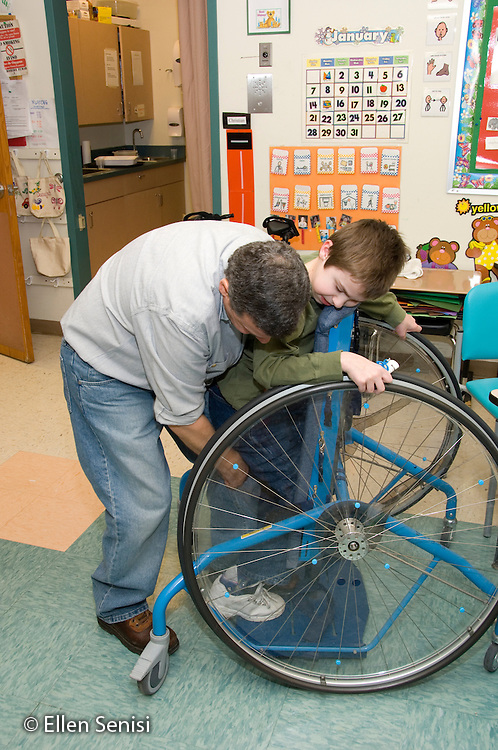 MR / Albany, NY.Langan School at Center for Disability Services .Ungraded private school which serves individuals with multiple disabilities.Teaching assistant helps position child in his Mobile Prone Stander. Boy: 10, Duchenne muscular dystrophy, expressive and receptive language delays.MR: Bud2; Sai2.© Ellen B. Senisi