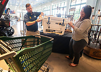 Reed Tucker (left) manager of Bass Pro Shop in Rogers helps Becky Roark, executive director of the Beaver Watershed Alliance load a cooler full of fishing supplies Thursday June 10, 2021. The supplies as well as 70 rods and reels were donated by Bass Pro Shop for an event scheduled for spring of 2022 called Big Bass Bonanza at Beaver Lake. The fishing gear will be distributed to children attending the event which was postponed from spring of 2021 due to high water at the lake. For more information see www.beaverwatershedalliance.org Visit nwaonline.com/2100611Daily/ and nwadg.com/photo. (NWA Democrat-Gazette/J.T. Wampler)