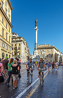 Urban Street Photography. <br /> A busy street in Rome, Italy. The cyclists and the pedestrians depict the vibrance that is Rome. <br /> The textured lighting on the buildings, and the Statue of Santa Maria Maggiore combined with blue, sky speak of a warm and busy summer day in Rome. <br /> The pedestrians and the cyclists anchor the scene to the background of the photograph. <br /> The deep shadows that are cast from the buildings add drama and interest to the photograph.