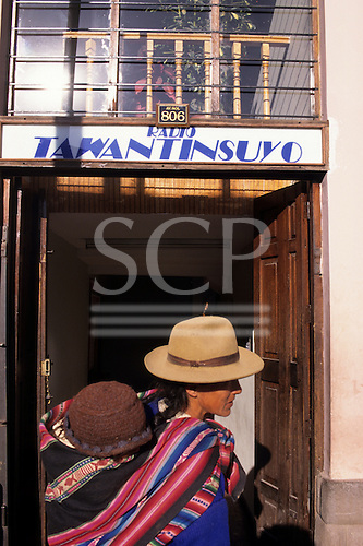 Cusco, Peru.  Woman in traditional clothes carrying a child on her back, Cusco Radio station is in the background.