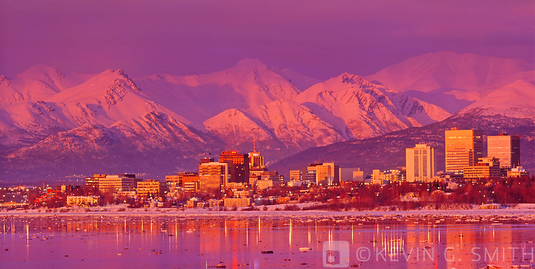 A photo of the Anchorage skyline at sunset with alpenglow on the Chugach Mountains and the buildings reflected in the water, as seen from Earthquake park, winter, Southcentral Alaska, USA.