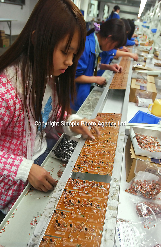 """Factory workers assemble circuit boards at Zhuhai Aimei Electronic Technology Co., Ltd. which is a MP3 and MP4 factory in Zhuhai city , Guangdong Province, China. MP3 players are coveted items among young adults in China. Students and young professionals rank a MP3 at top of their """"must buy"""" electronics list in 2006. ."""