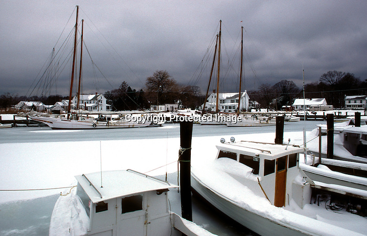 Skipjacks and other work boats are frozen in an icy Dogwood Harbor, Tilghman Island,MD