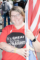 """LaBeccah Davis, of Longview, Texas, wears a shirt reading """"It's Great to be Straight / Genesis 1"""" and holds a Straight Pride flag before marching in the Straight Pride Parade in Boston, Massachusetts, on Sat., August 31, 2019."""