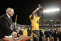 Jahvid Best holds up the MVP trophy, as Gary Cavali looks on, .2008 Emerald Bowl, San Francisco, Calif., Saturday, Dec. 27, 2008. University of California 24, University of Miami, 17.