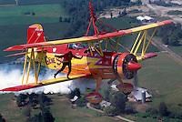 "Wingwalker (Teresa Stokes) wingwalking on Gene Soucy's Grumman Ag Cat Biplane ""Showcat"" - at Abbotsford International Airshow, BC, British Columbia, Canada"