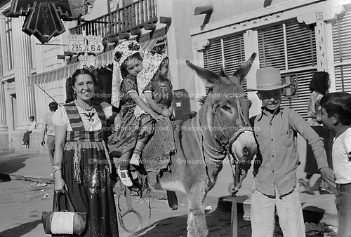 0405-N03. Indian woman with children riding a burro in a Santa Fe, NM parade.  They are on Rt. 285/64/84, date is approximately 1940s.  Curio shop on right, bank building on left.