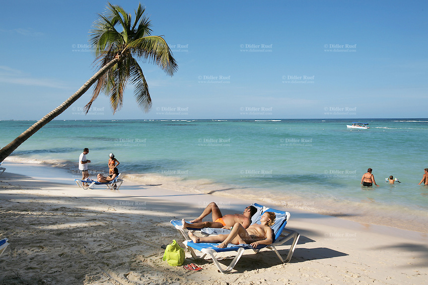 Dominican Republic. La Altagracia Province. Coastal resort of Punta Cana. Playa Bavaro. El Cortecito. Hotel Carabela Bavaro. Family holiday. A couple lays on  deckchairs near the beach. They are enjoying the sun and sunbathes. Blue sky. Punta Cana is well-known for its beaches and palm trees where meet whites sands and warm turquoise water from the Atlantic Ocean.  © 2006 Didier Ruef
