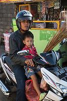 Jimbaran, Bali, Indonesia.  Young Man and Young Boy on Motorbike, no Helmet on Boy.