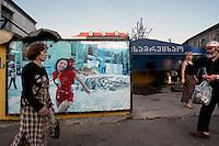 People walk past an advertising billboard in Batumi......
