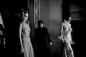 Paris, France.Behind the stage Russian fashion designer Valentine Yudashikin watches his show at the Carrousel du Louvre in Paris on a TV monitor with his co-workers and models coming off and on the stage..
