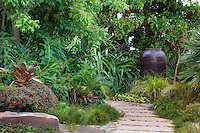 Stepping stone path leading to urn focal point in backyard foliage tapestry garden; Sherry Merciari garden