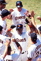 SAN FRANCISCO, CA - Barry Bonds of the San Francisco Giants is greeted by his teammates in front of the dugout at Candlestick Park in San Francisco, California on July 22, 1993. (Photo by Brad Mangin)